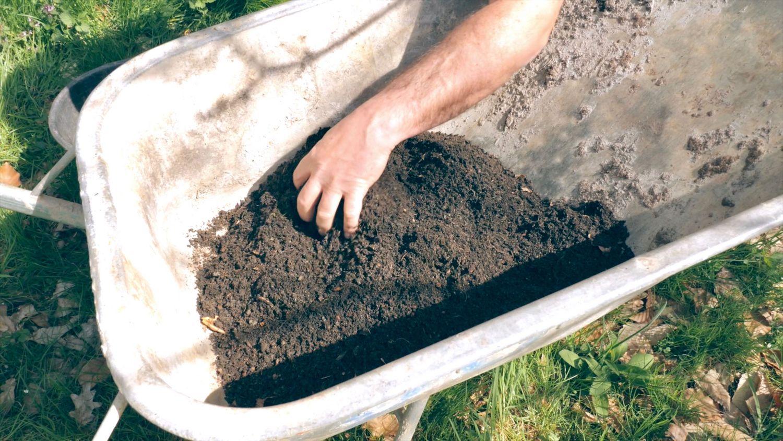 Gerald Dunst mischt in Scheibtruhe seinen Kompost vom Hausgarten