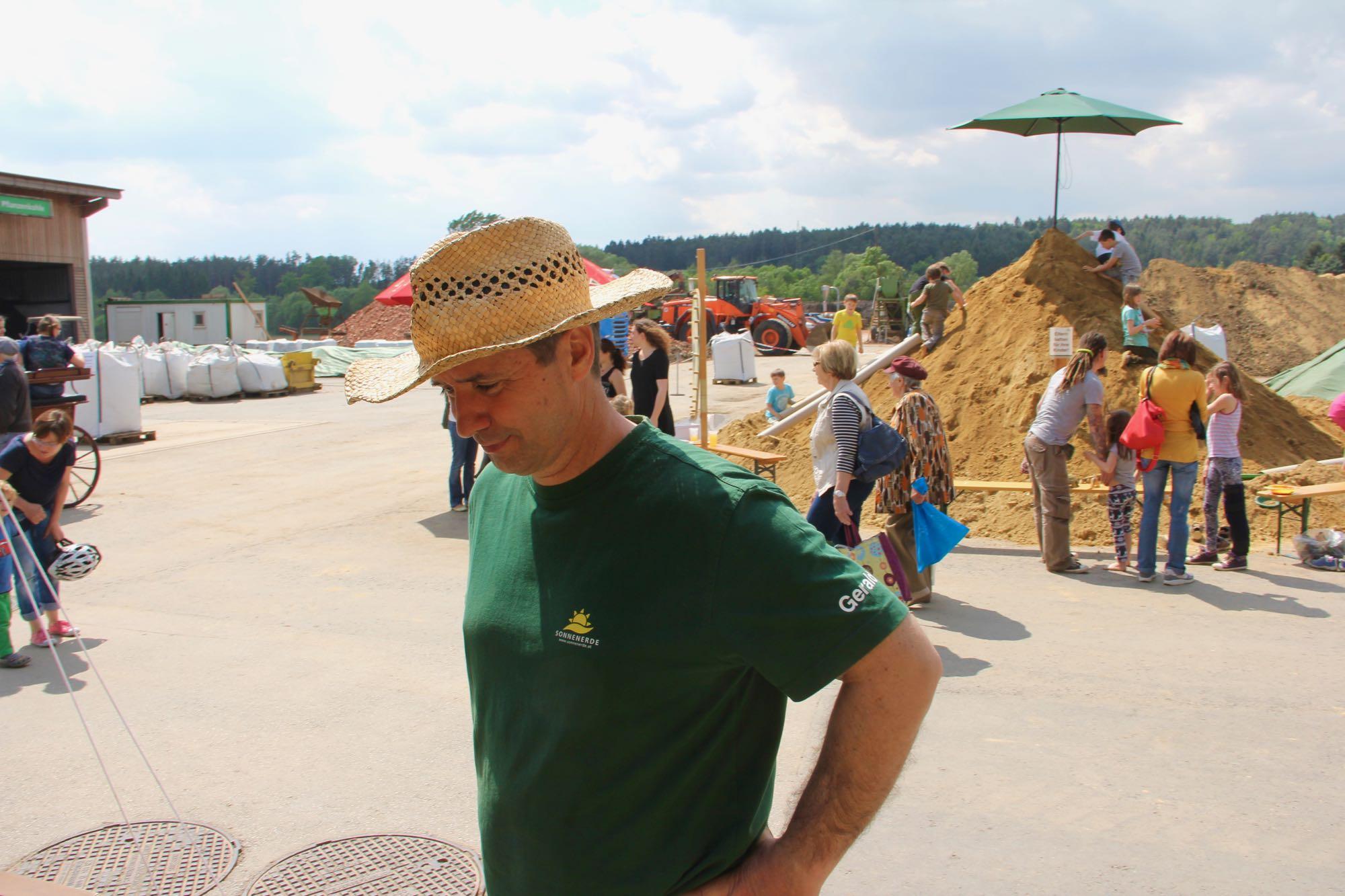 Gerald Dunst mit Hut vor dem Riesen-Sandhaufen mit spielenden Kindern