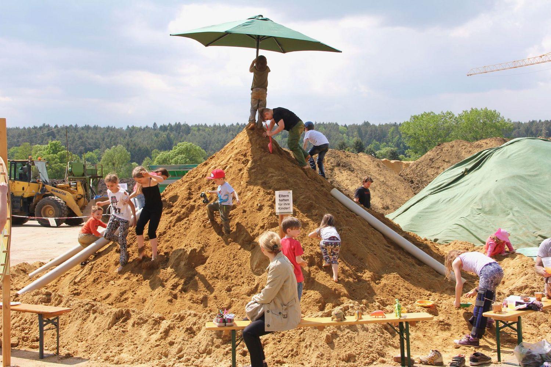 Detailfoto vom Riesen-Sandhaufen mit spielenden Kindern beim Tag der offenen Tür bei Sonnenerde