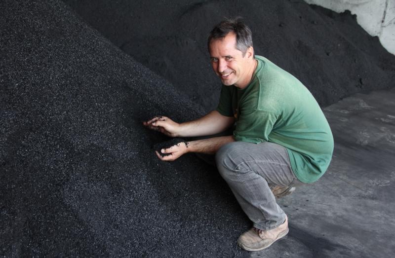 Gerald Dunst, stolz vor dem Pflanzenkohle Haufen